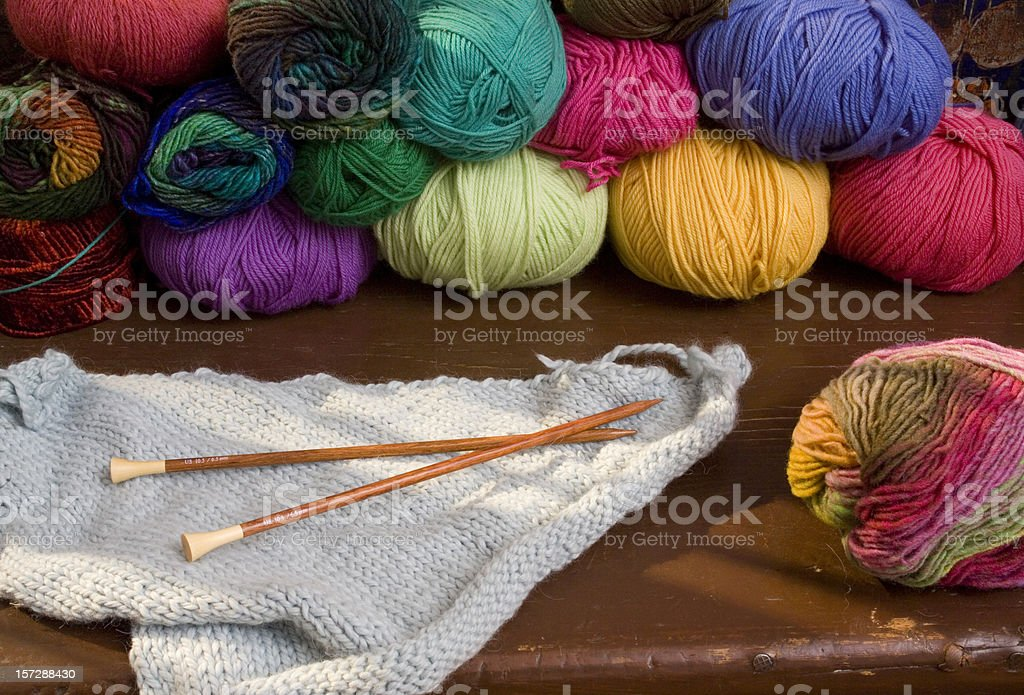Colorful spools of yarn and the start of a blue knit blanket royalty-free stock photo