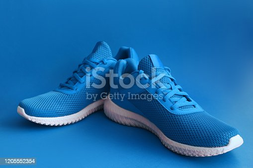 istock Colorful sport shoes on blue color backround 1205552354