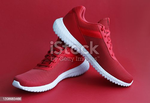 Colorful sport shoes on red color backround. Modern fashion sneakers print concept