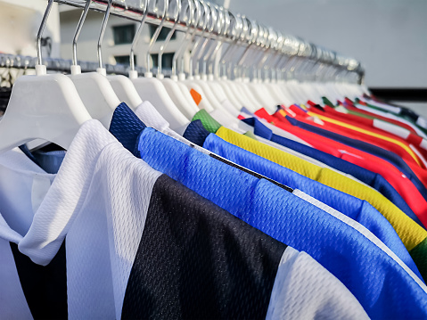 Colorful sports team shirts hanging at clothes rails