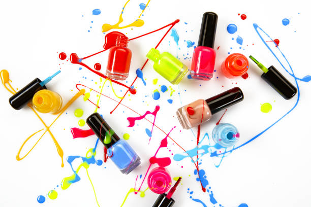 Colorful spray of nail polish from glass bottles as an abstract painting stock photo
