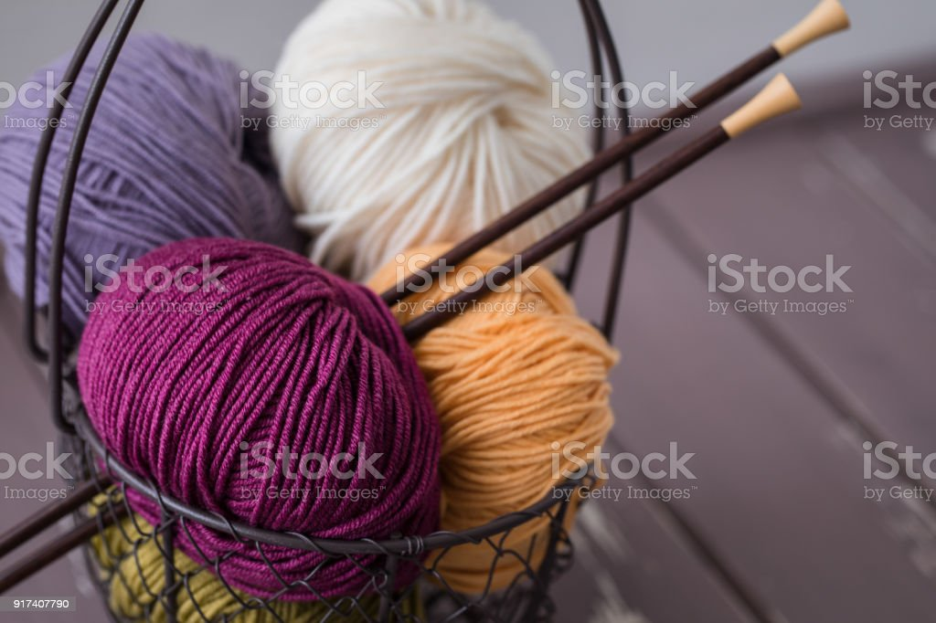 Colorful spring wool yarn in an iron basket with wooden knitting needles stock photo
