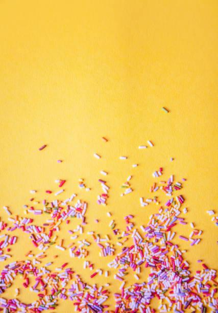 colorful sprinkle texture background, yellow, vertical, with copy space - posypka zdjęcia i obrazy z banku zdjęć