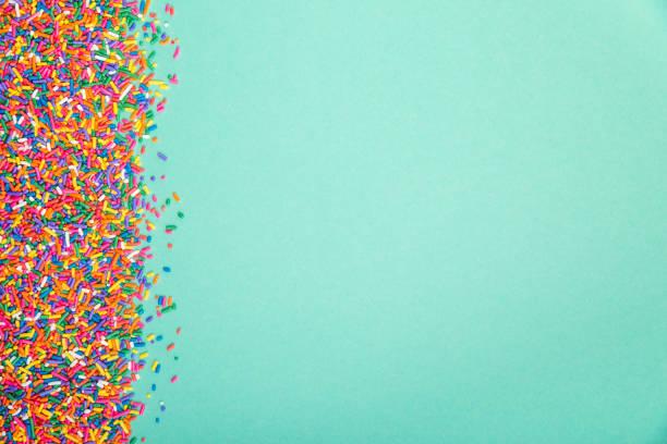 colorful sprinkles on edge of green background - posypka zdjęcia i obrazy z banku zdjęć