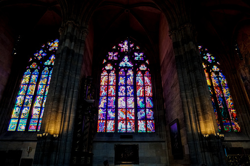 Colorful stained glass window in st. Vitus Cathedral in Prague, Czech Republic. Concept of Gothic interior decoration.