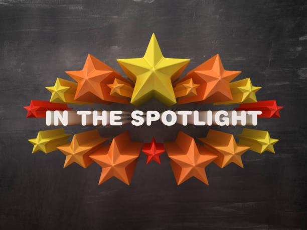 Bunte Sterne mit IN DER SPOTLIGHT Phrase auf Tafel Hintergrund - 3D Rendering – Foto