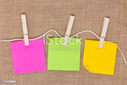 istock Colorful sticky notes with clothespins on burlap background. 174426664