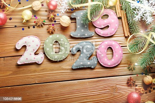 istock Colorful stitched digits 2019 2020 of polkadot fabric with Christmas decorations flat lyed on wooden background 1054018896