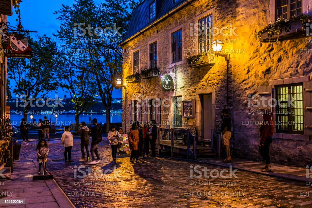 Colorful stone buildings on street during twilight in lower old town with people stock photo