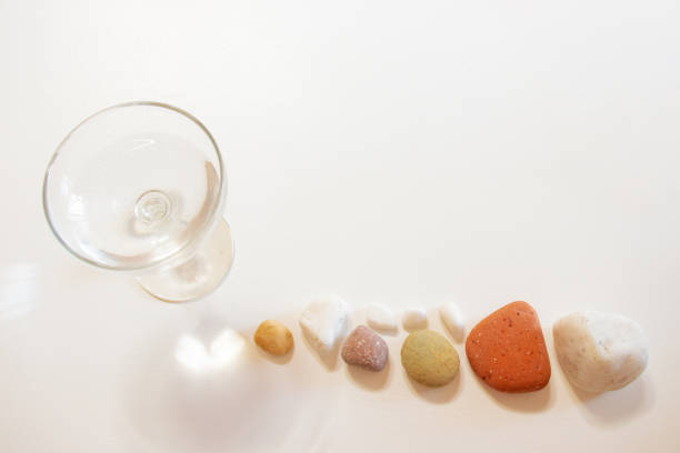 Colorful stones, a heart shape and a glass of water on a white table. stock photo