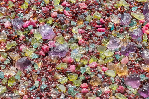 istock Colorful stones background - pile of semi precious jewelery stones 668987024