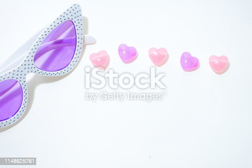 Colorful stones in heart shape and sunglasses on the white background