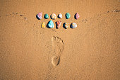 Colorful volcanic stones with footprint on a sandy beach. View from above.