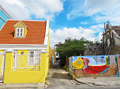 Buildings in the Pietermaai District in the city of Willemstad, Curacao, date back to the early 1700s. The district fell into disrepair, but a full-scale revitalization at the end of the 20th Century has turned the neighbourhood into a trendy area with cafes, boutique hotels, shops and restaurants. Many of the historic buildings have been decorated with public art, like this mural which commemorates the 150th anniversary of the abolition of slavery.