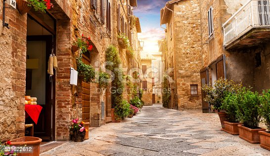 Colorful street in Pienza with many decoration flowers and trees, Tuscany, Italy
