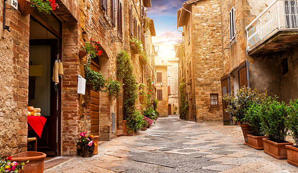 Colorful street in Pienza, Tuscany, Italy Colorful street in Pienza with many decoration flowers and trees, Tuscany, Italy pienza stock pictures, royalty-free photos & images