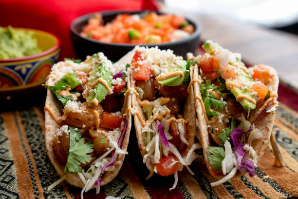 Colorful Street Tacos, Shrimp - Seafood, Fish, Grilled, Ready-To-Eat A beautiful arrangement of shrimp tacos with pico de gallo, avocado, cilantro, chipotle sour cream, and cotija cheese taco stock pictures, royalty-free photos & images
