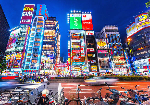 Colorful streets of Shinjuku area, Tokyo, Japan Colorful streets of Shinjuku shopping district with blurred commuters at dusk  electronic billboard stock pictures, royalty-free photos & images