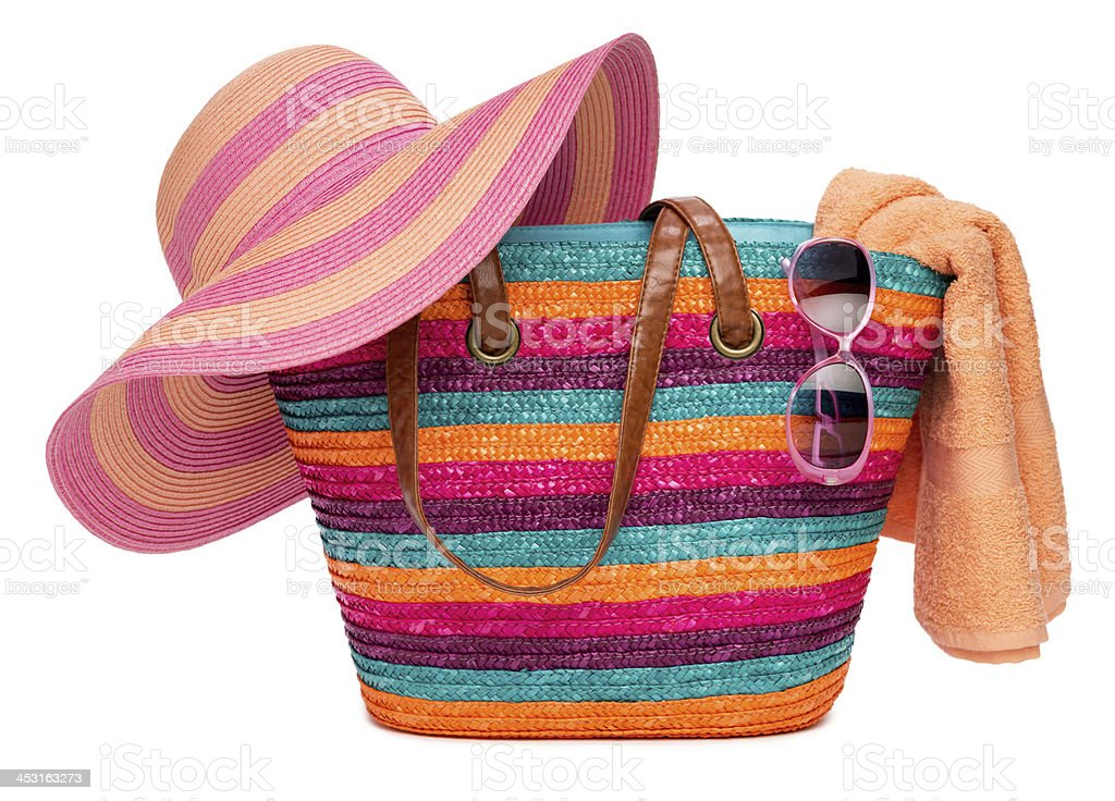 Colorful striped beach bag with straw hat towel and sunglasses bildbanksfoto