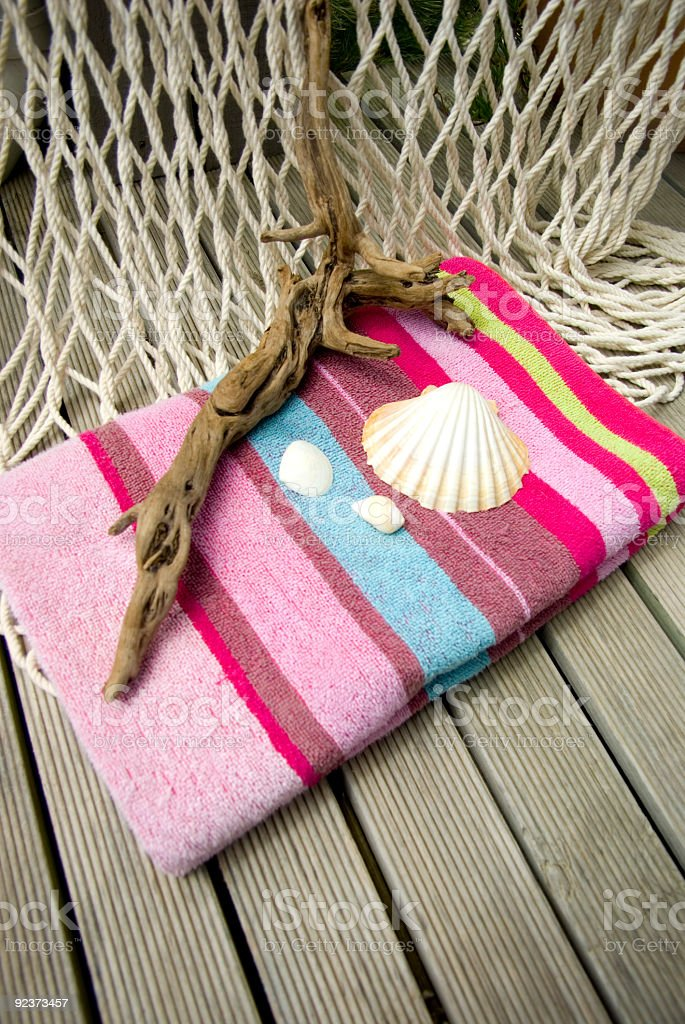 Colorful striped Beach towel on wooden deck with sea shells royalty-free stock photo