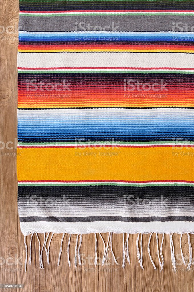 Colorful striped Mexican blanket on wooden floor stock photo
