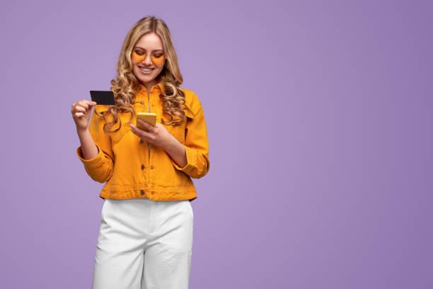 Colorful stylish woman enjoying online shopping stock photo