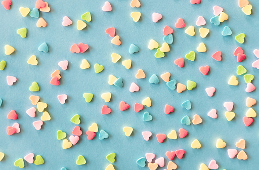 Colorful sugar heart shaped sprinkles frame on green blue background. Valentines day concept.