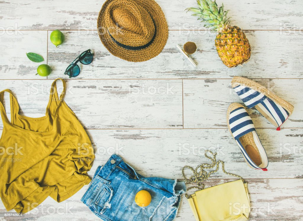 Colorful summer fashion outfit flat-lay over parquet background, copy space stock photo
