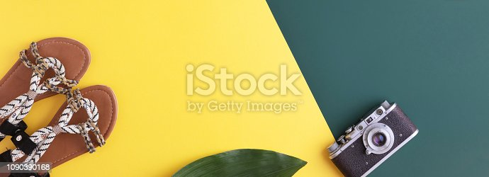 Colorful summer female fashion outfit flat lay. Straw hat, sunglasses, palm leaf over yellow background, top view, copy space. Summer fashion holidays flat lay