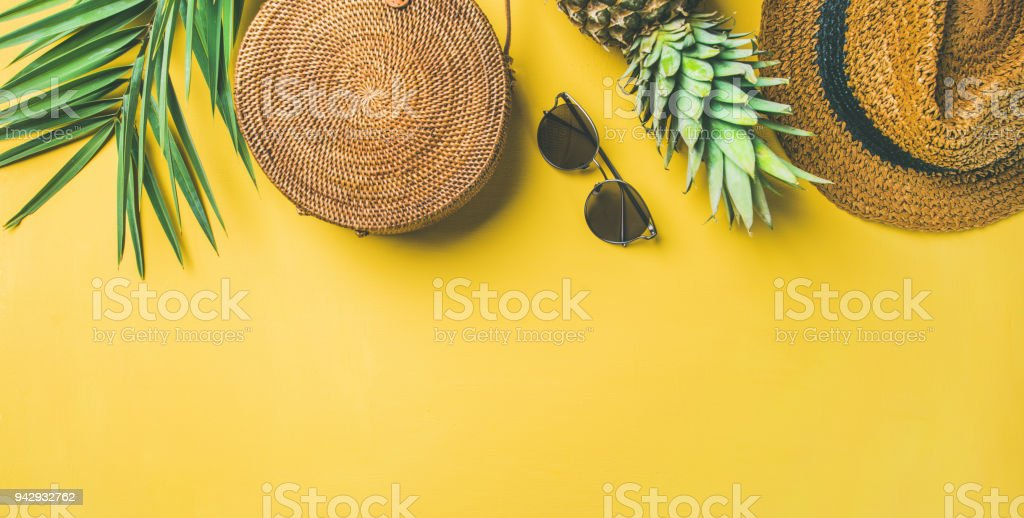 Colorful summer female fashion outfit over yellow background, wide composition stock photo