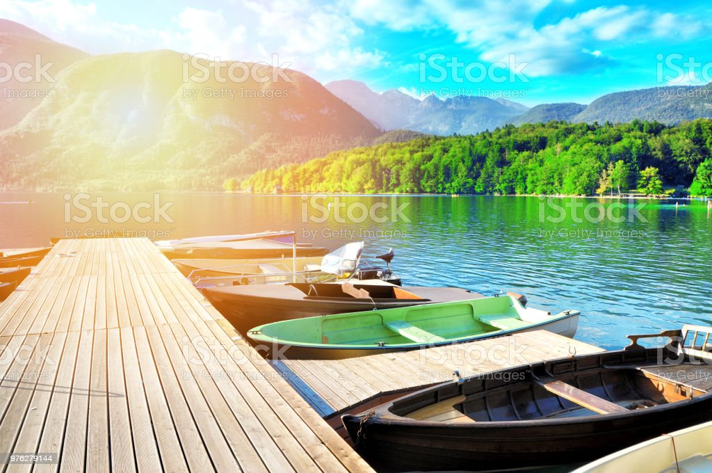 Colorful summer on the Bohinj Lake. Moning sun light in the Triglav National Park, Julian Alps, Slovenia.A pier with boats on a clear crystal water with beautiful nature in background. stock photo