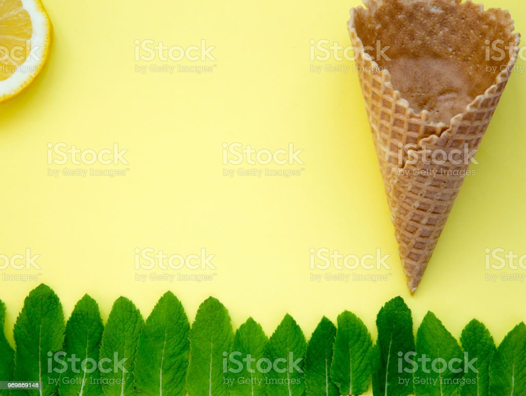 Colorful summer pattern. Mint leaves and sweet waffle cone and slice of lemon on yellow background. stock photo