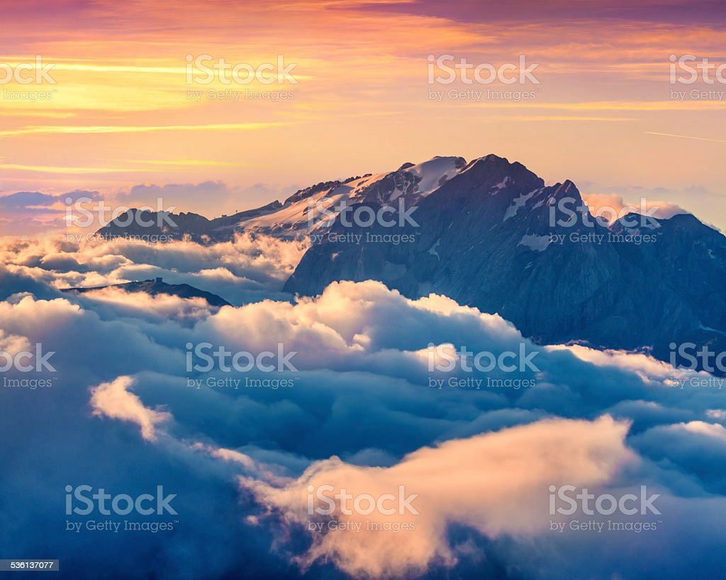 Colorful summer sunrise on the foggy Val di Fassa valley stock photo