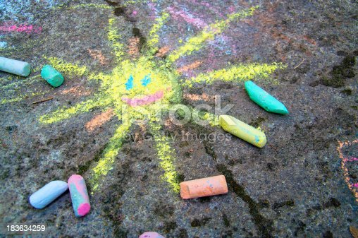 istock Colorful sun drawn on asphalt with sidewalk chalk 183634259