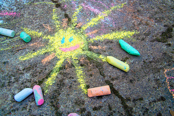 colorful sun drawn on asphalt with sidewalk chalk - chalk drawing stock photos and pictures