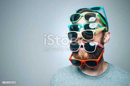 A portrait of a man with a large beard, wearing multiple pairs of multi-colored sunglasses.  Studio shot; horizontal with copy space.