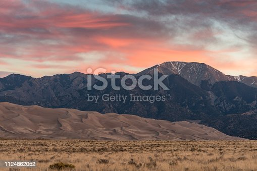 Colorful Sunrise at Great Sand Dunes National Park and Preserve with pink skies and mountains in the background