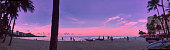 Colorful sunrise at Waikiki beach, Honolulu, Hawaii. There are people, surfboards and traditional polynesian boats on the edge. Panoramic view.