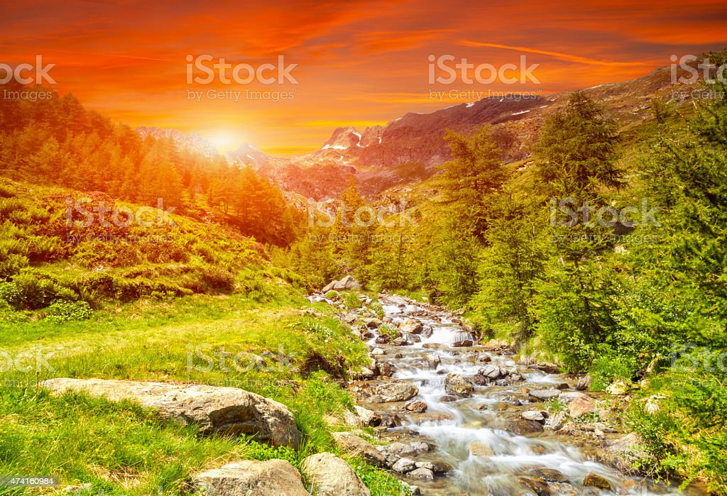 Colorful sunset and a river in the Alps stock photo