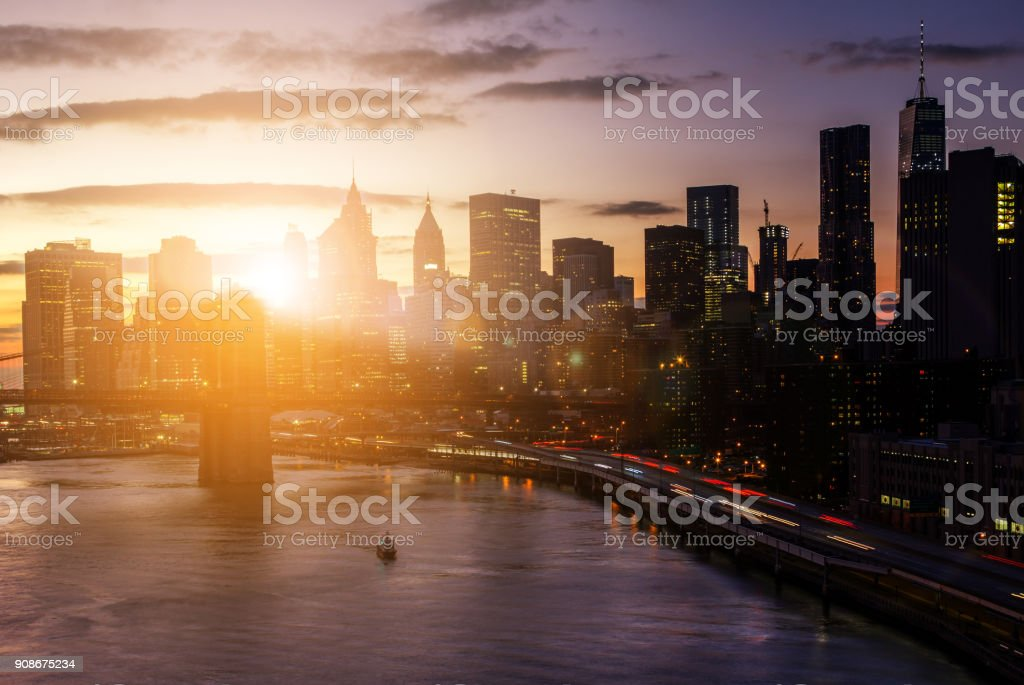 Colorful sunset behind the Brooklyn Bridge and skyscrapers in New York City stock photo