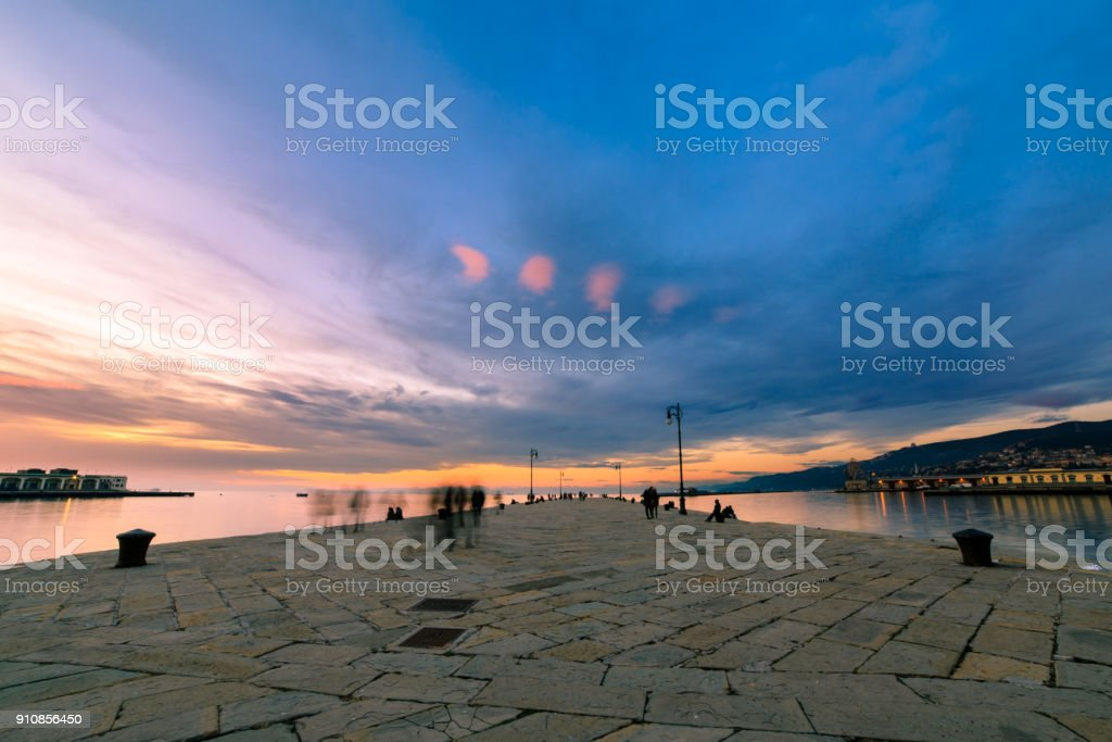Colorful sunset in front of the city of Trieste stock photo