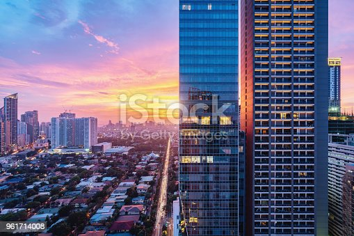 Colorful vibrant sunset over Makati in Downtown Manila. Aerial view along city road towards the sun. Modern skyscrapers in the foreground. Makati, Manila, Philippines, Asia.
