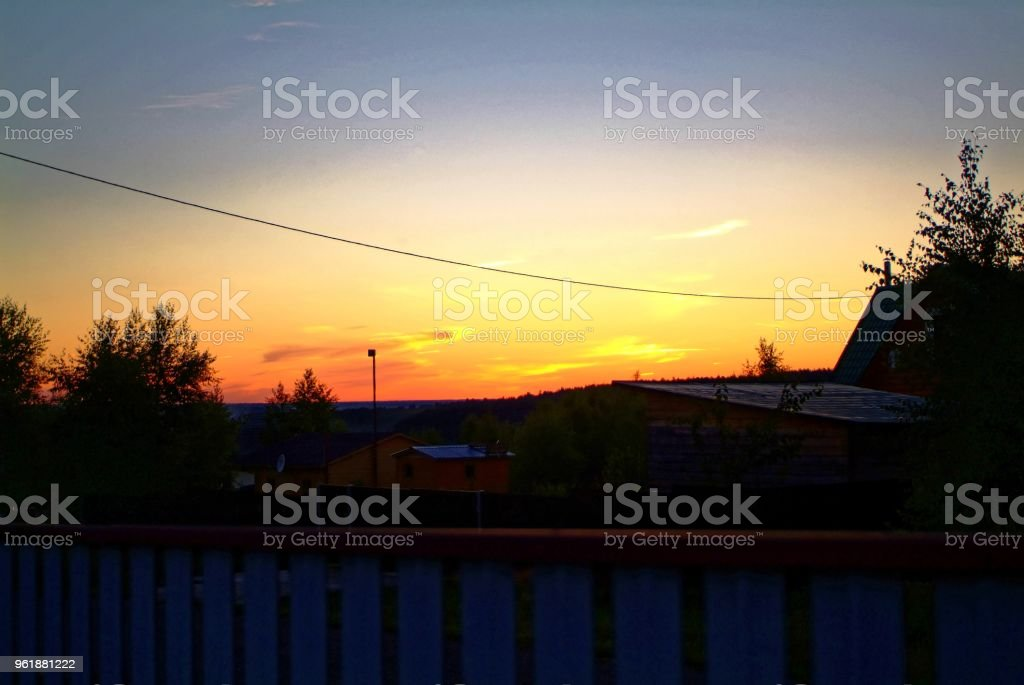 colorful sunset on a background of trees stock photo