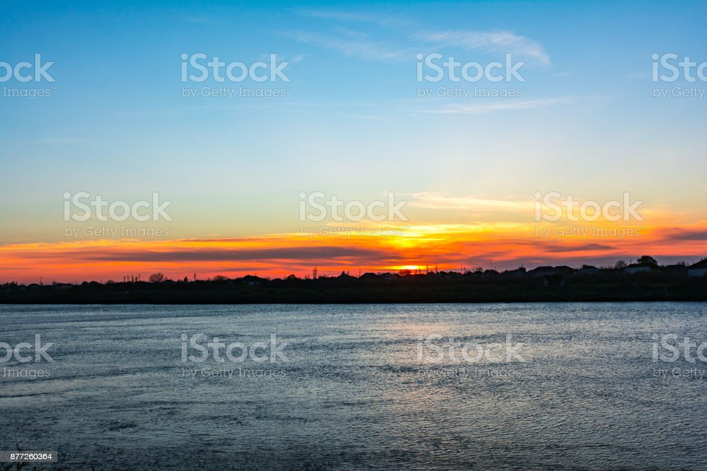 Colorful sunset on plain river stock photo