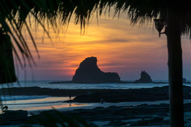 farbenprächtigen sonnenuntergang am strand in nicaragua mit einem stein in der front. - nicaragua stock-fotos und bilder