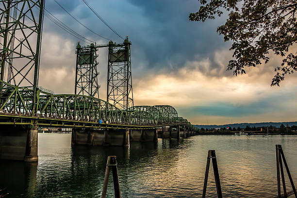 Colorful Sunset Over Columbia River Oregon Washington Bridge Dense Clouds Beautiful sunset featuring dense clouds over the Interstate Bridge. A drawbridge spanning the Columbia River.  Portland, Oregon and Hayden Island is to the south as viewed from the Washington State side of the river in Vancouver, WA. Riverfront, Waterfront, No People, Horizontal landscape. USA washington state stock pictures, royalty-free photos & images