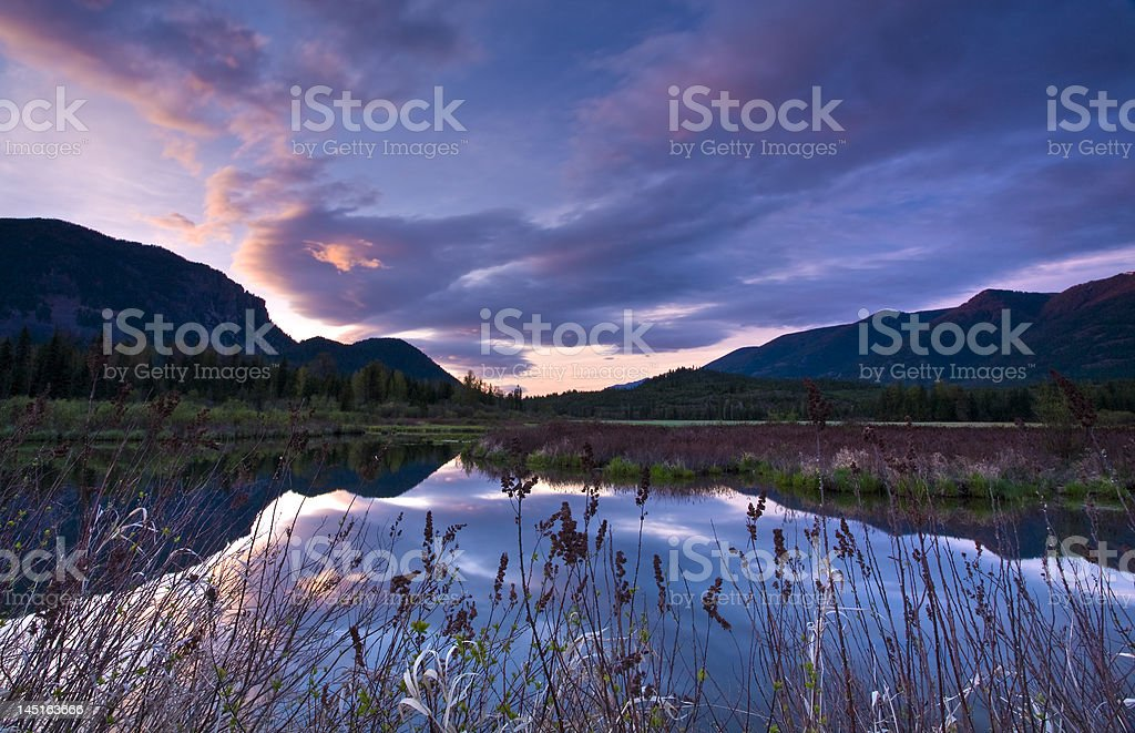 Colorful sunset over marsh with motion capture of clouds stock photo