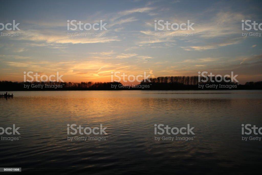 kleurrijke zonsondergang over de rivier de Rotte in Zevenhuizen met weerspiegeling in het water in Nederland foto