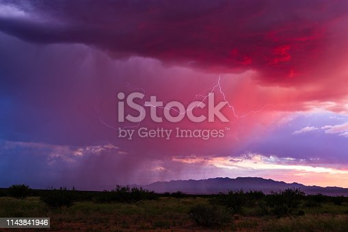 1039163636 istock photo Colorful sunset sky with rain and lightning 1143841946