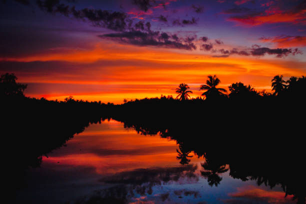 farbenprächtigen Sonnenuntergang mit Wolken Lichtstrahlen über den Fluss mit Reflexionen über Silhouette Natur Landschaft Hintergrund – Foto